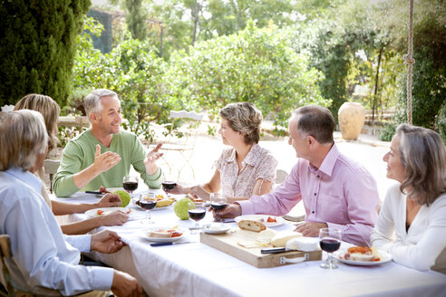 Spain, Mallorca, six friends sitting at laid table in the garden - RMAF000115