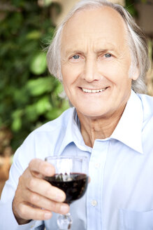Portrait of relaxed senior man holding glass of red wine - RMAF000118