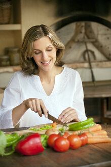 Portrait of smiling woman chopping vegetables - RMAF000142