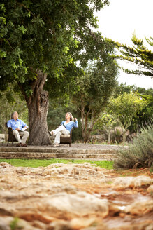 Spain, Mallorca, couple relaxing under a tree in their garden - RMAF000145