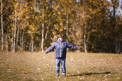 Little boy enjoying sunlight with outstretched arms - MMFF001269