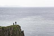 UK, Northern Ireland, County Antrim, people on rock cliff at Causeway Coast - EL001685