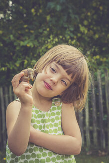 Portrait of smiling little girl holding vineyard snail - LVF004078