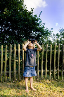 Little girl standing on a meadow watching something with binocular - LVF004081