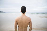 Spain, Galicia, Ferrol, shirtless man looking on the sea - RAEF000592