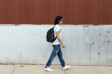 Man with a backpack walking on the sidewalk - GIOF000363