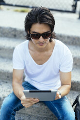 Man sitting on steps using digital tablet - GIOF000369