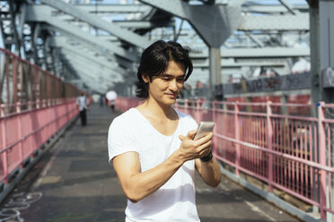 USA, New York City, man on Williamsburg Bridge in Brooklyn checking the cell phone - GIOF000375