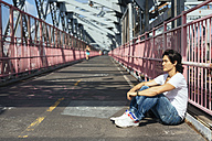 USA, New York City, man relaxing on Williamsburg Bridge in Brooklyn - GIOF000378