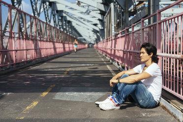 USA, New York City, man relaxing on Williamsburg Bridge in Brooklyn - GIOF000378
