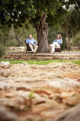 Couple sitting on chairs under a tree - RMAF000159