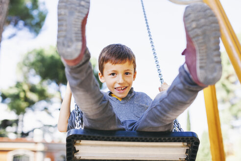 Happy boy on a swing at the playground - EBSF000995