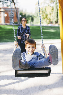 Happy boy on a swing at the playground - EBSF000998