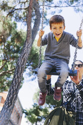 Mother pushing son on a swing at the playground - EBSF001001