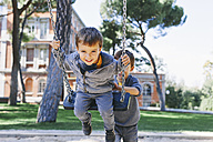 Boy pushing brother on a swing at the playground - EBSF001004