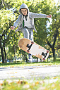 Boy doing a skateboard trick in park in autumn - DEGF000563