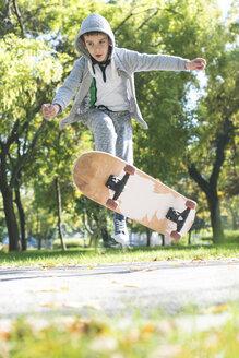 Boy doing a skateboard trick in park in autumn - DEGF000563