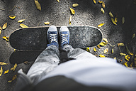 Boy standing on skateboard on path with autumn leaves - DEGF000569