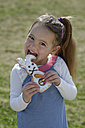 Portrait of smiling little girl biting off pastry formed like an Eastern Bunny - LBF001274
