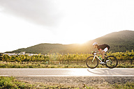 Cyclist riding a bike on a road - JRFF000162