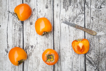 Whole and sliced kaki persimmons and a kitchen knife on wood - LVF004097