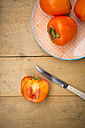 Whole and sliced kaki persimmons and a kitchen knife on wood - LVF004100
