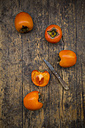 Whole and sliced kaki persimmons and a kitchen knife on wood - LVF004103