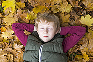 Portrait of boy with closed eyes relaxing on autumn leaves on the ground - SARF002258