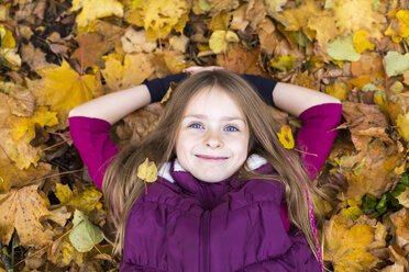 Portrait of smiling girl relaxing on autumn leaves on the ground - SARF002264