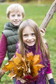 Portrait of girl holding bunch of autumn leaves while her brother standing in the background - SARF002270
