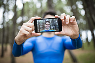 Selfie of a runner on the display of a smartphone - RAEF000606