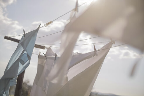 Laundry hanging on clothesline in sunlight - RIBF000345