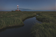 Germany, Schleswig-Holstein, North Sea Coast, View of Westerheversand Lighthouse in the evening - KEBF000256