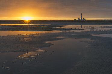 Germany, Schleswig-Holstein, North Sea Coast, View of Westerheversand Lighthouse, tideland at sunrise - KEBF000259