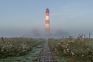 Germany, Schleswig-Holstein, North Sea Coast, View of Westerheversand Lighthouse in the fog - KEBF000280