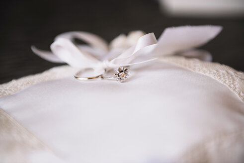 Wedding rings on a white chushion, close-up - GEMF000456