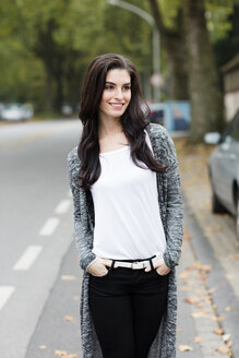 Portrait of smiling young woman with hands in her pockets - GDF000886