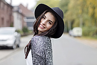 Portrait of smiling young woman wearing black hat looking over her shoulder - GDF000889