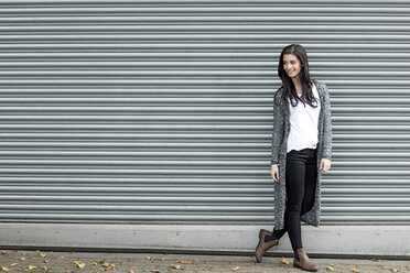 Smiling young woman standing in front of roller shutter - GDF000892