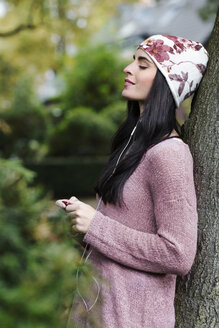 Portrait of young woman leaning against tree trunk hearing music with earphones - GDF000895