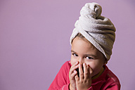 Portrait of little girl covering  mouth with her hands wearing towel turban - ERLF000070