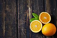 Sliced and whole orange on dark wood - CSF026641