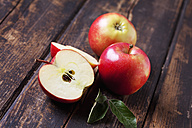 Whole and sliced red apples on dark wood - CSF026644