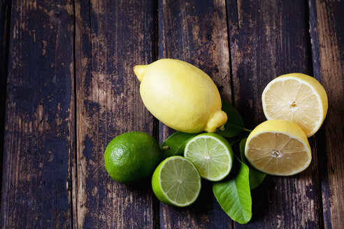 Whole and sliced lemons and limes  on dark wood - CSF026647