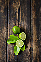 Whole and sliced limes with leaves on dark wood - CSF026650
