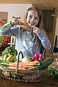 Portrait of girl with wickerbasket of fresh vegetables at home - SARF002276