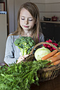 Portrait of girl with wickerbasket of fresh vegetables looking at broccoli - SARF002282