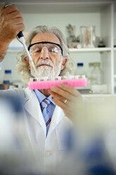 Senior professor filling sample glasses in laboratory - RMAF000184