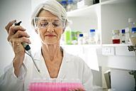 Female professor filling sample glasses in laoratory - RMAF000187