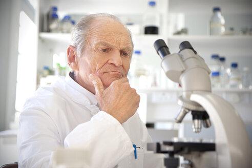 Professor in laboratory examining samples under microscope - RMAF000193